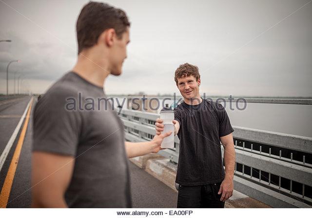 Junger Mann Übergabe Wasserflasche an Freund Stockbild