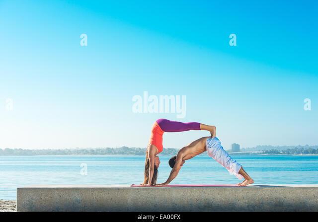 Junger Mann und Frau praktizieren Yoga am Pacific Beach, San Diego, Kalifornien, USA Stockbild