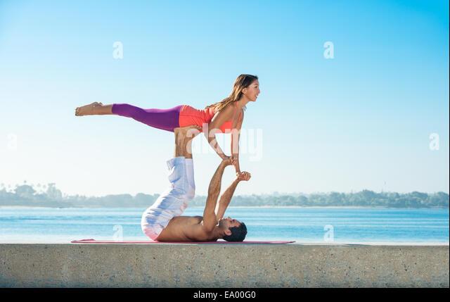 Junger Mann und Frau praktizieren Yoga am Pier in Pacific Beach, San Diego, Kalifornien, USA Stockbild
