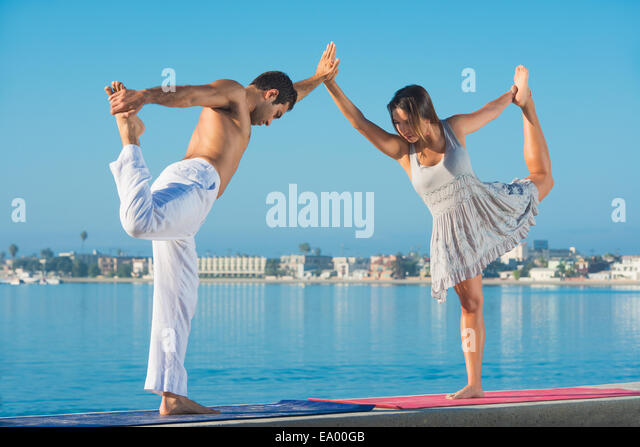 Junger Mann und Frau üben Yogaposition am Pacific Beach, San Diego, Kalifornien, USA Stockbild