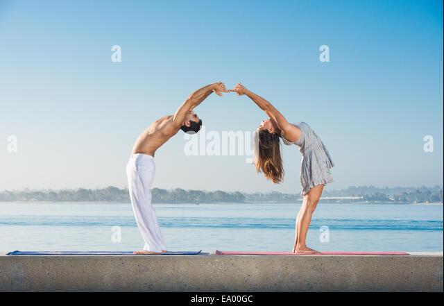 Junger Mann und Frau beim Yoga am Pacific Beach, San Diego, Kalifornien, USA Stockbild