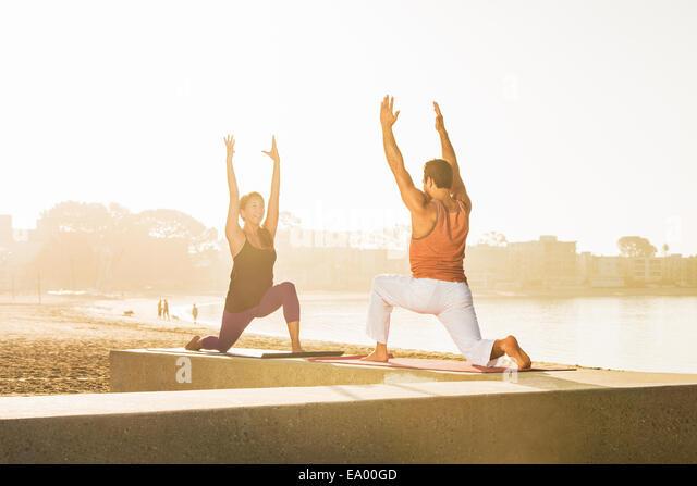 Junger Mann und Frau beim Yoga am Pier in Pacific Beach, San Diego, Kalifornien, USA Stockbild