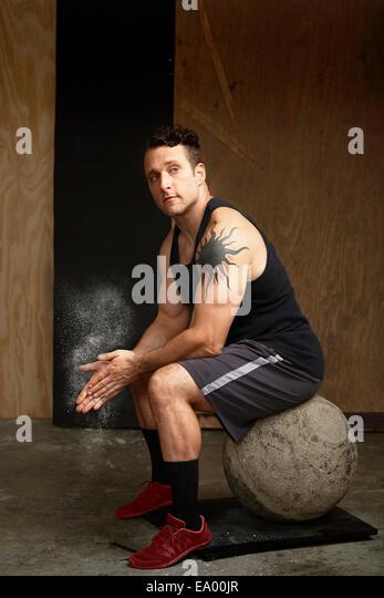 Porträt von Mitte erwachsenen Mann sitzt auf Atlas Ball im Fitness-Studio Stockbild