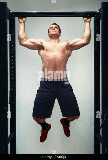 Mitte Männchen tun Pull Ups auf Übung Bar im Fitness-Studio Stockbild