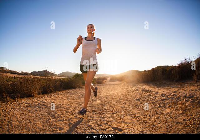 Junge Frau Joggen auf sonnigen Weg, Poway, Kalifornien, USA Stockbild