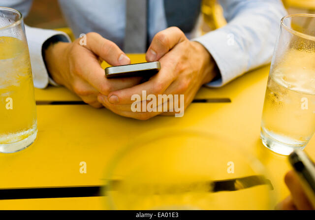 Hände des Jünglings SMS auf Smartphone im Straßencafé Stockbild