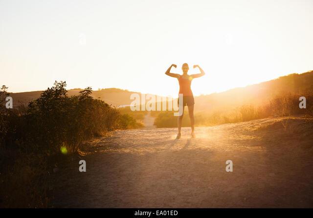 Weibliche Jogger beugen der Arme im Sonnenlicht, Poway, Kalifornien, USA Stockbild