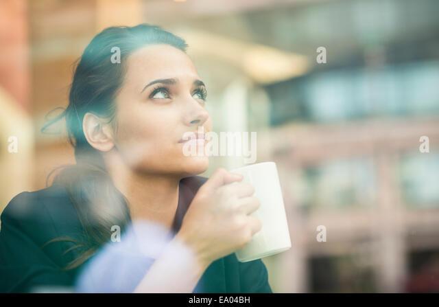 Geschäftsfrau, trinken Kaffee und Blick aus Café Fenster, London, UK Stockbild