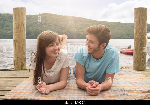 Junge, lächelnde paar liegen auf Decke auf Steg am See Stockbild