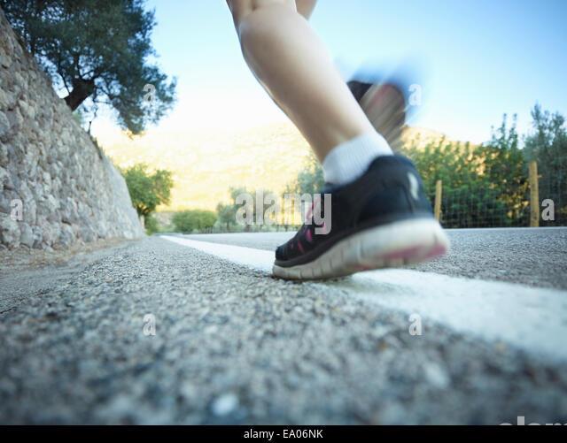 Ebene Oberflächenansicht von Mädchen im Teenageralter Beine laufen auf Straße, Mallorca, Spanien Stockbild
