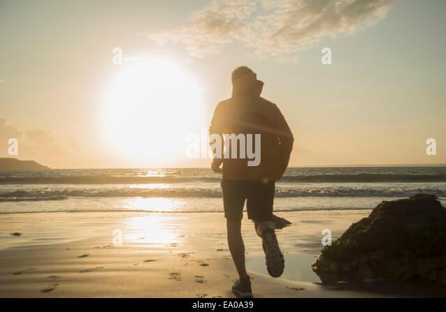 Reifer Mann, Strand entlang laufen Stockbild