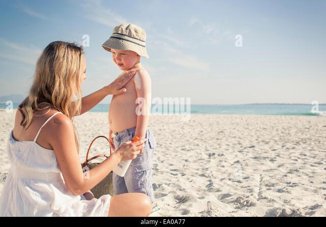 Mitte Erwachsene Mutter Sonne Eincremen zu kleinen Sohn auf Beach, Cape Town, Western Cape, Südafrika Stockbild