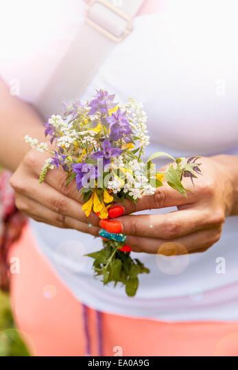 Junge Frau mit wilden Blumen Stockbild