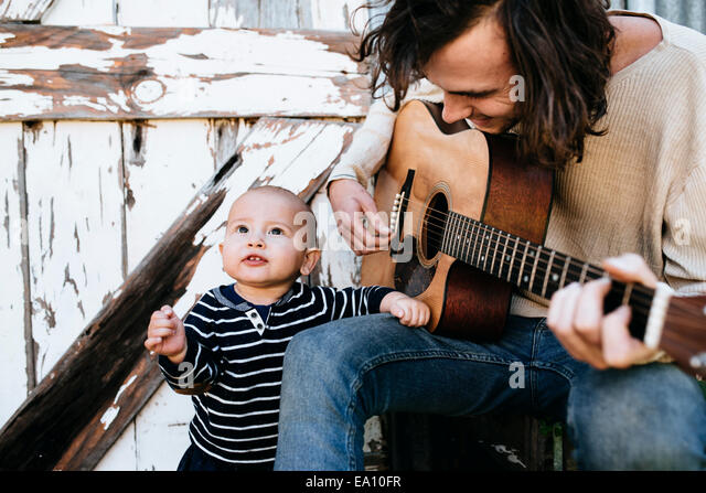 Unterhaltsame Vater Sohn mit Gitarre Stockbild