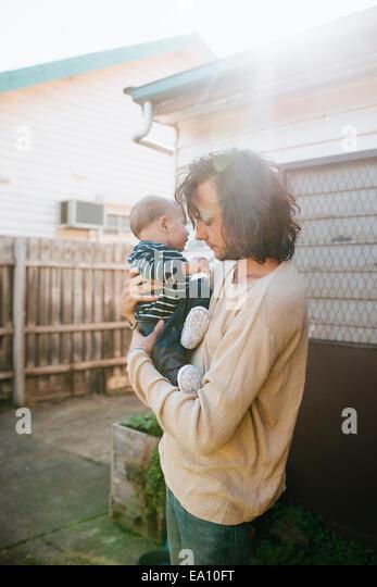 Vater mit Sohn in Armen neben Haus Stockbild
