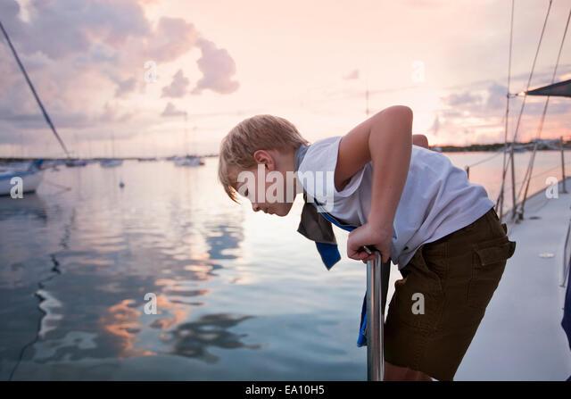 Junge auf Segelboot blickte auf das Meer bei Sonnenuntergang Stockbild