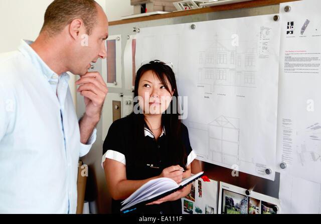Männliche und weibliche Architekten betrachten Baupläne im Büro Stockbild