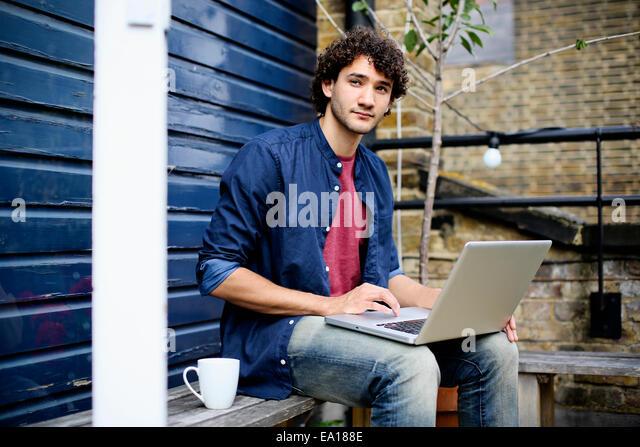 Mann mit Laptop auf Bank Stockbild