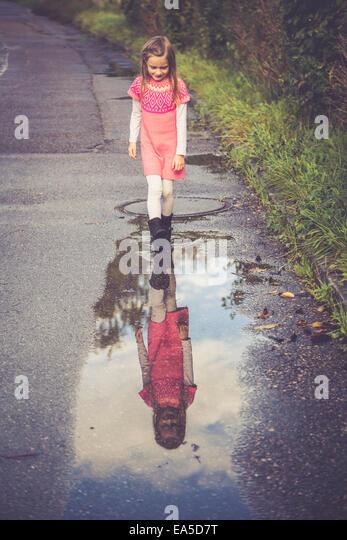 Kleines Mädchen Blick auf ihr Spiegelbild in einer Pfütze Stockbild