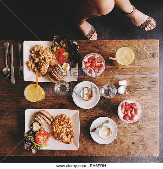 Draufsicht auf die Beine und Frau Frühstückstisch Stockbild