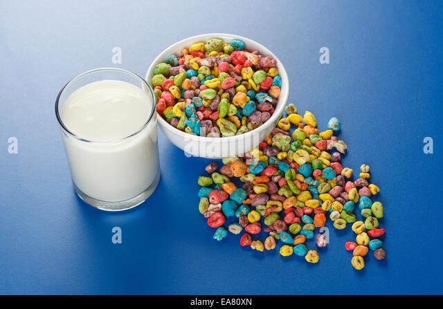 Ungesunde Lebensmittel: tauchte Weizensamen mit vielen künstlichen Farbstoff und Glas Milch Stockbild