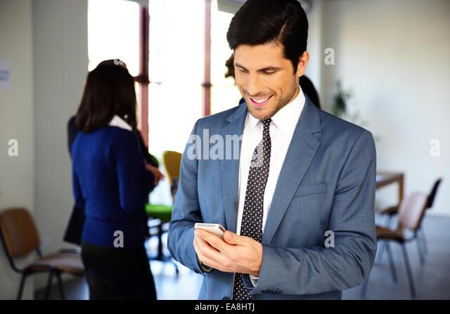 Lächelnde Geschäftsmann mit Smartphone im Büro Stockbild
