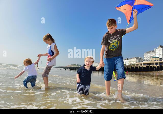 Kinder, die entlang dem Strand bei Ebbe. Eastbourne, East Sussex. UK Stockbild