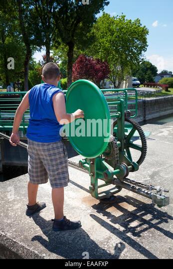Ein Junge, der Betrieb der Schleuse Öffnungsmechanismus Rad auf dem Fluss Charente in Jarnac Stockbild