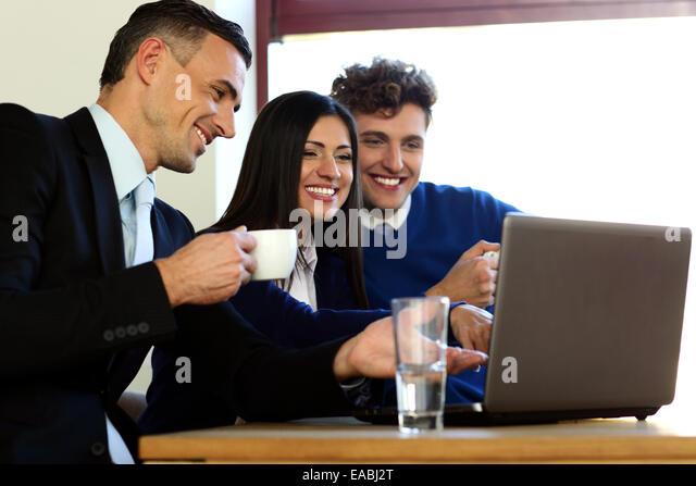 Geschäftsleute, die mit Laptop zusammen im Büro Stockbild