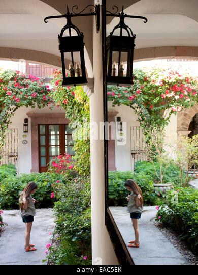 junges Mädchen im Garten mit Halle Spiegel Stockbild