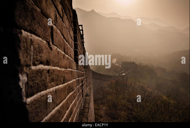Die Great Wall Of China erhebt sich bei Sonnenuntergang über die umliegende Landschaft bedeckt durch Smog bei Stockbild