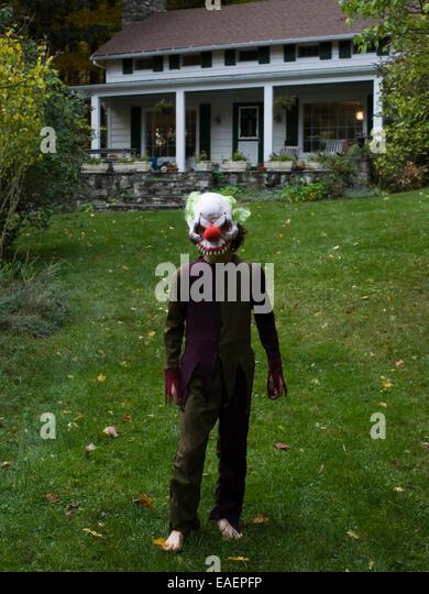 Junge im Halloween-Kostüm und Maske auf Wiese vor Haus Stockbild