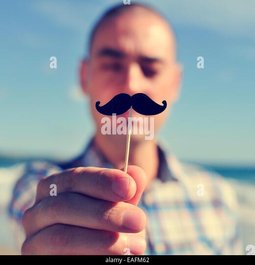 ein junger Mann einen falschen Schnurrbart in einem Stock vor sein Gesicht hält Stockbild