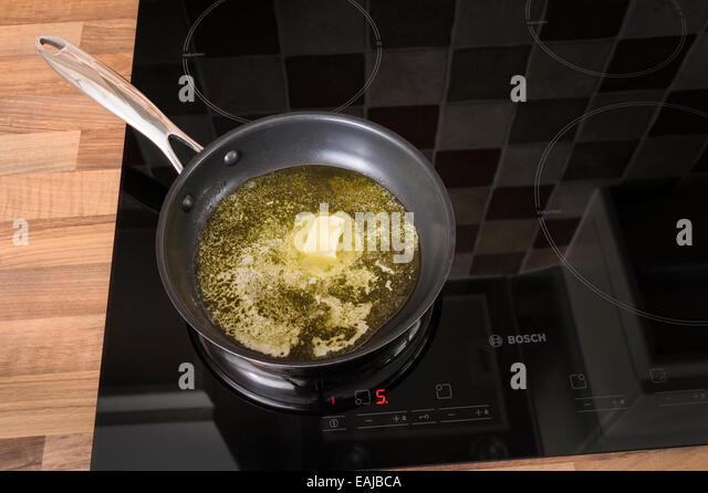 Butter in einer Pfanne auf einem Induktionskochfeld schmelzen. Ungesund, Cholestrol. Stockbild