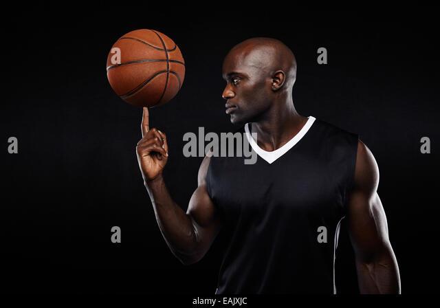 Porträt des jungen afrikanischen Athleten Ausgleich Basketball an seinem Finger auf schwarzem Hintergrund. Stockbild