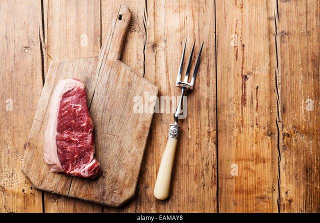 Rohes Frischfleisch Striploin Steak und Fleischgabel auf hölzernen Hintergrund Stockbild