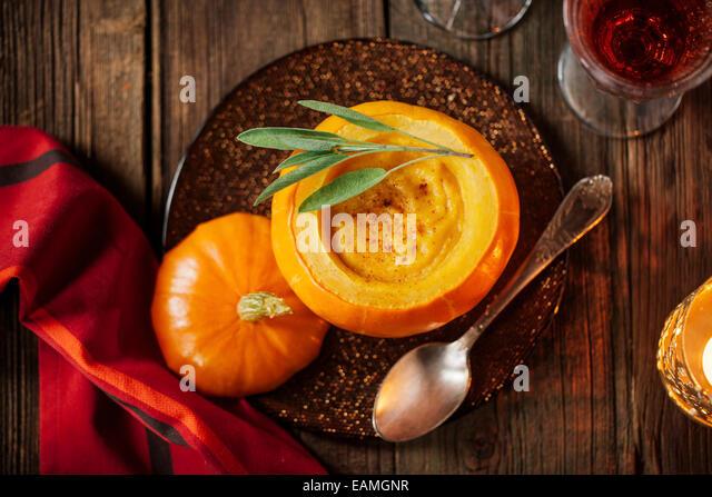 Kürbissuppe in einem kleinen Kürbis mit Blatt Salbei Stockbild