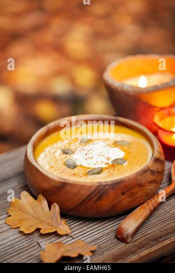 Kürbissuppe in einer rustikalen Schüssel außerhalb im Herbst Stockbild