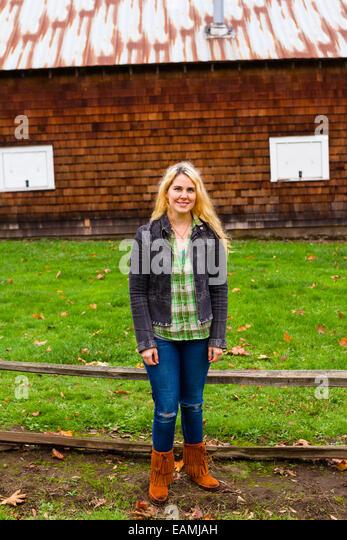 Lifestyle Portrait einer Frau im Freien mit einer Scheune im Hintergrund. Stockbild