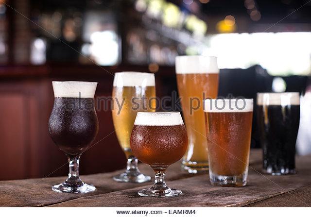 Eine Auswahl an Bieren in eine Vielzahl von Gläsern auf einem rustikalen Holz Oberfläche mit bar im Hintergrund. Stockbild