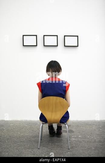 Eine Künstlerin, die auf einem Stuhl sitzend ein Kunstwerk betrachten. Stockbild