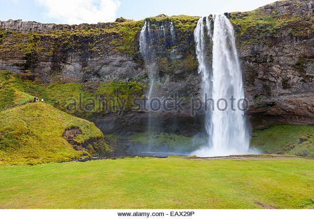 Seljalandsfoss Wasserfall Kaskadierung über eine Klippe in einer Landschaft von elektrischen grüner Vegetation. Stockbild