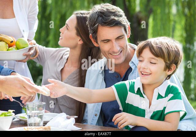 Gesunde Mahlzeit im Freien, gemeinsames Essen Familie Vater Holding Sohn auf Schoß Stockbild