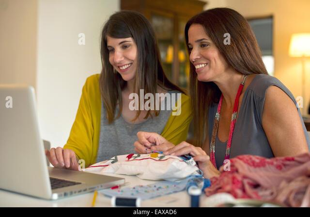 Schwestern gemeinsam lernen Stickerei durch Online-Videos Stockbild