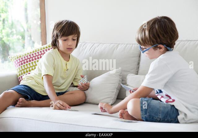 Jungen sitzen auf Sofa Spielkarten Stockbild