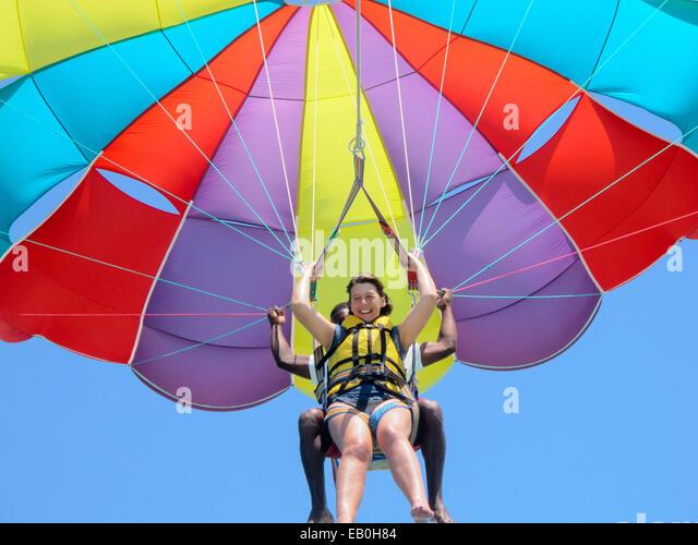 Eine Frau mittleren Alters in ihren 50ern, parasailing oder Drachenfliegen, mit Hilfe, Mauritius Stockbild