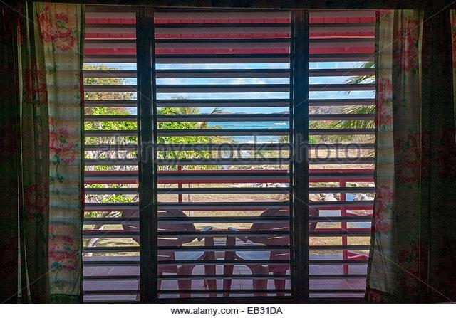 Ein Blick durch die Lamellen aus einem Fenster Schatten in einem Guest House auf Virgin Gorda. Stockbild