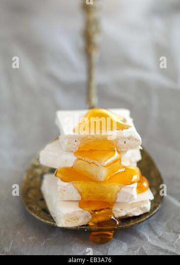 Quadratische Stücke von weißen, plain Nougat im Stapel auf Metalllöffel in beträufelt Honig Stockbild