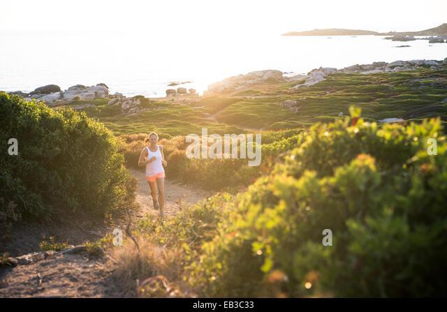 Frankreich, Korsika, Frau Trailrunning an Küste Stockbild