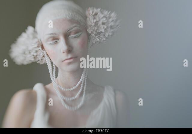 Portrait von junge Frau trägt Make up, Schminke, Perlen und Ohr Dekorationen ähneln Blütenstand mit Stockbild